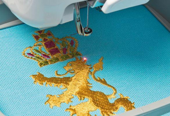 Roter LED-Pointer auf goldenes Löwen-Stickmuster auf blauem Stoff