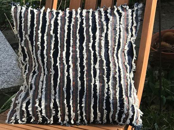 Zerrissenes Kissen aus Jeansstreifen auf Holzstuhl