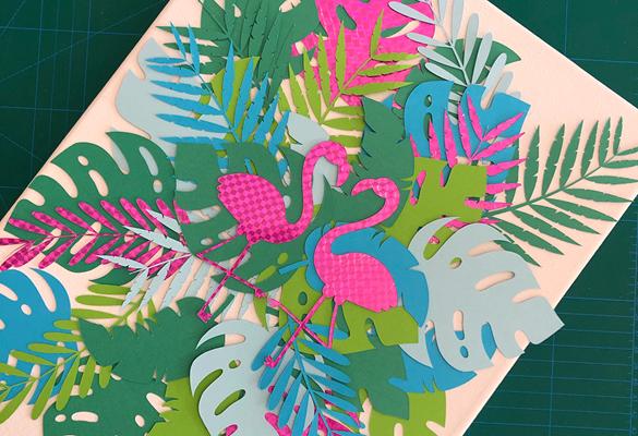 Два розовых бумажных фламинго на красочных листах большой зеленой бумаги