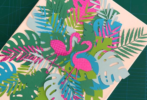Zwei rosa Papierflamingos auf bunten großen grünen Papierblättern