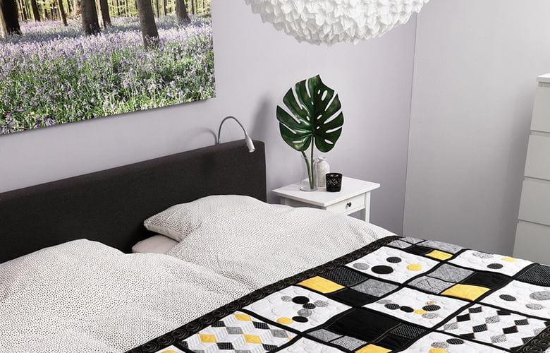 Zwart, geel en grijs dekbed op een bed in een lichte kamer