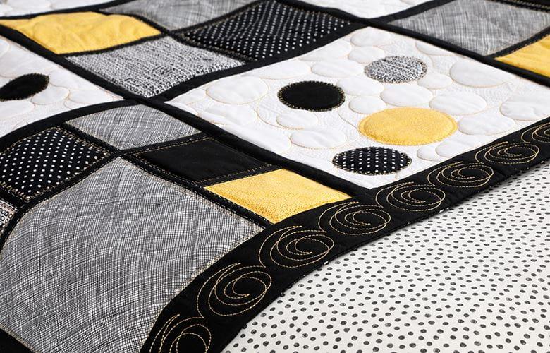 close-up van zwart, geel en grijs quilt bedrunner