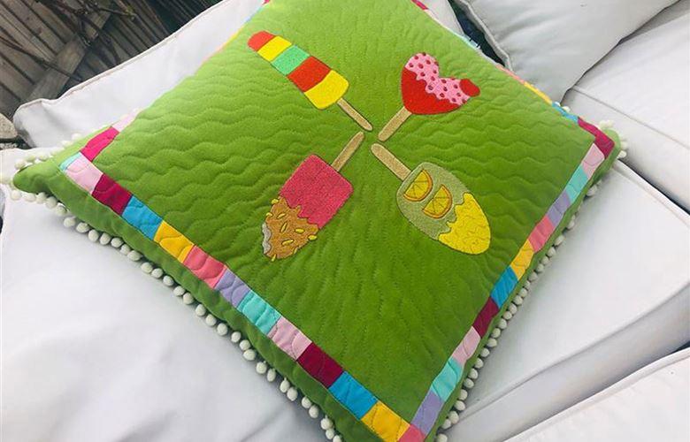 Grünes Kissen mit bunten Eismotiven bestickt