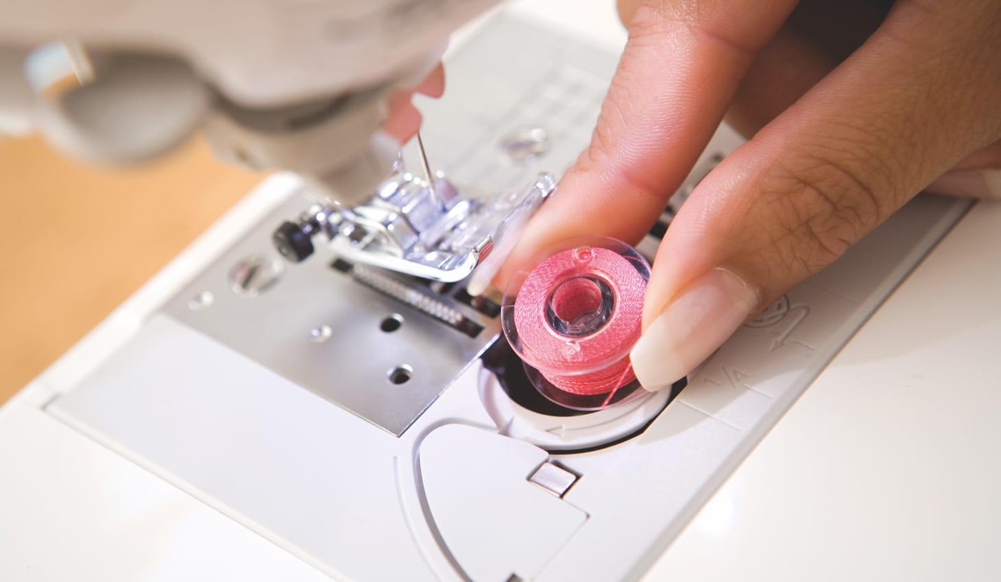Iemand vervangt de spoel op een naaimachine