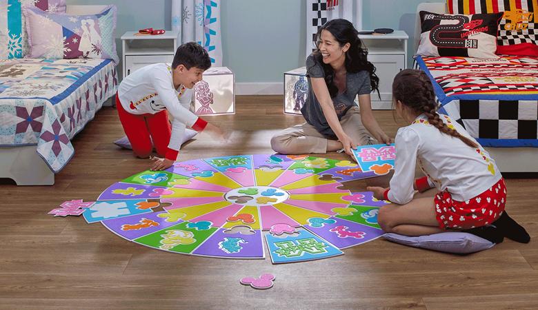 Maman, fille, fils construisant un tapis de jeu Mickey