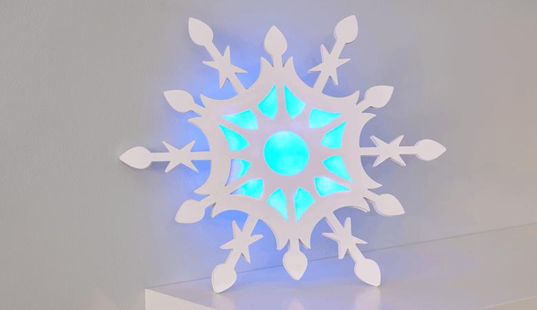 Grand flocon de neige découpé avec de la lumière bleue