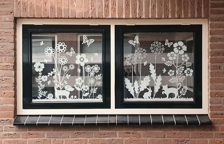 close-up van witte raamstickers van bloemen en dieren