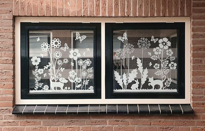 Nahaufnahme von weißen Fensteraufklebern mit Blumen und Tieren