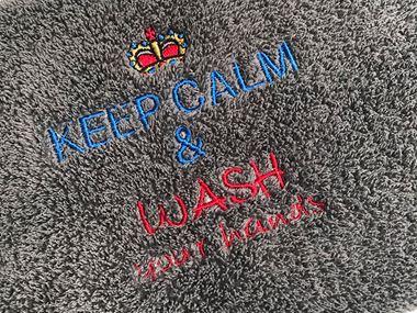 Graues Handtuch mit Bleib ruhig und wasche deine Hände Stickerei