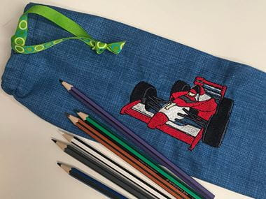 Red racecar embroidery on dark blue pencil case with pencils