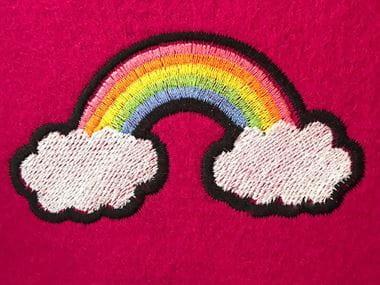 Arcobaleno colorato con terminazioni nuvola su sfondo rosa brillante