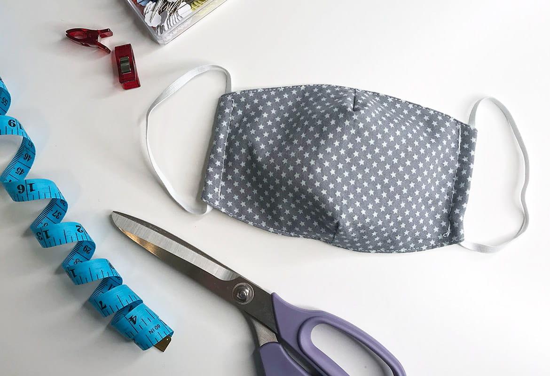 Masque en tissu bleu étoilé avec ruban à mesurer et ciseaux