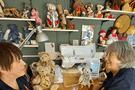 Two ladies with many teddybears around them.