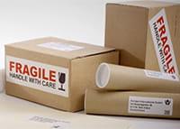 Štítky s adresou a varováním křehkého obsahu na hnědých krabicích