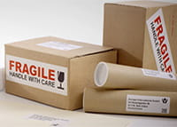 Address and fragile labels adhered to brown cardboard packaging