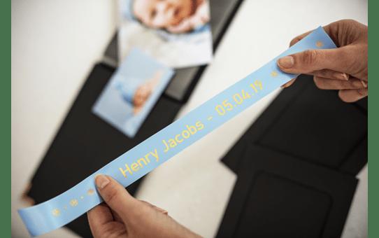 Äkta Brother TZe-RL54 satinbandskassett – guld på ljusblått, 24 mm brett band 4