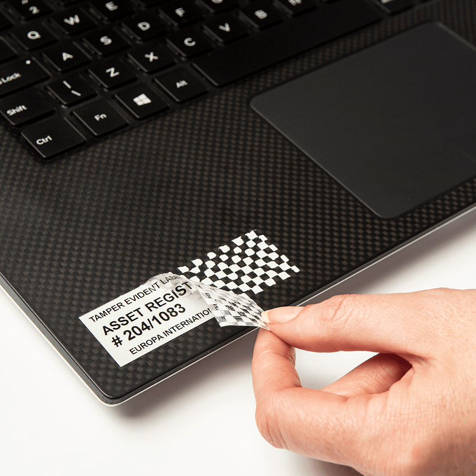 Brother TZe-SE5 tamper evident security tape cassette - black on white - tamper evident asset label being removed from a laptop, that cannot be reapplied once removed