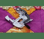 Pied de piqûre dans la couture en métal sur quilt violet-orange vif