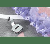 Pied fronceur en métal à côté d'un ruban organza froncé couleur lilas