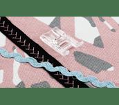 Pied en plastique F023N à côté d'un tressage cousu sur un ruban