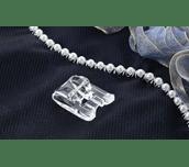 Pied pose-perles en plastique sur tissu sombre avec rangée de perles