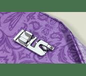 Rollsaumfuß F002N aus Metall auf violettem Stoff mit genähtem Rollsaum