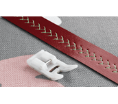 Pied anti-adhérent F007N à côté d'une bande de cuir cousue sur tissu