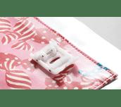Pied rouleau F066 sur tissu plastifié rose avec couture de bordure